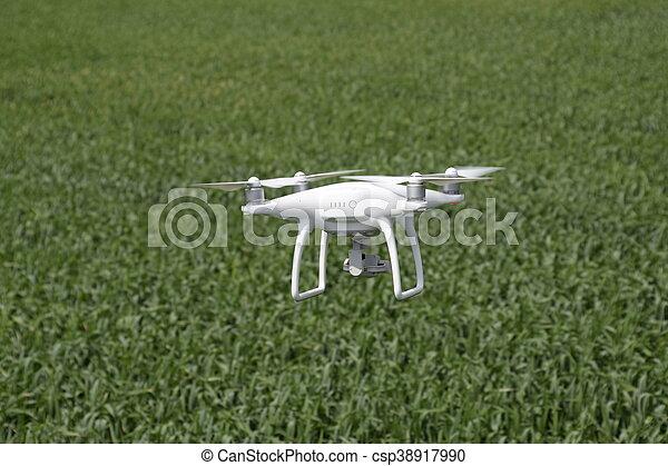 Cuadrocopteros blancos sobre un campo de trigo - csp38917990