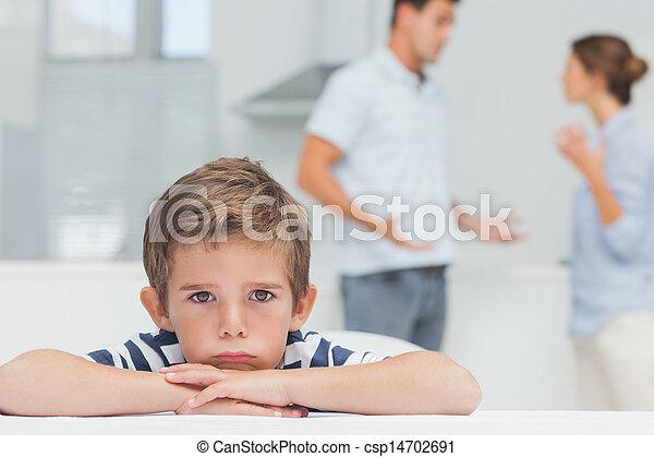Chico triste con los brazos cruzados mientras los padres discuten - csp14702691