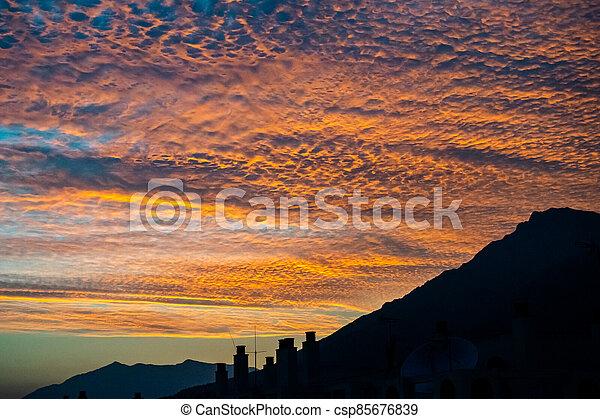 tropical autumn sunset with mountain range silhouette - csp85676839