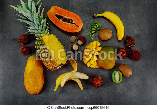 Tropical fruits assortment on a dark wood background with top view. - csp66018616