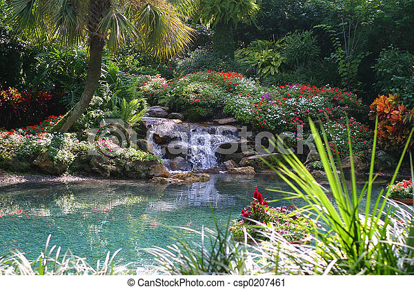 Tropical Pond Landscaped With Waterfall Surrounded By