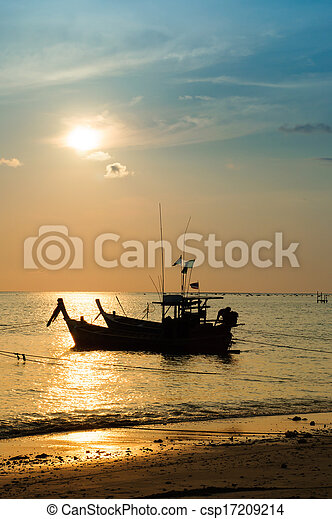 Tropical sunset and boat on the beach - csp17209214
