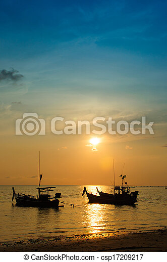 Tropical sunset and boat on the beach - csp17209217