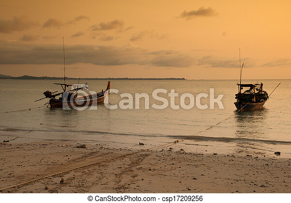 Tropical sunset and boat on the beach - csp17209256