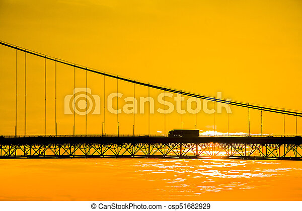 Truck crossing hanging bridge at sunset - csp51682929