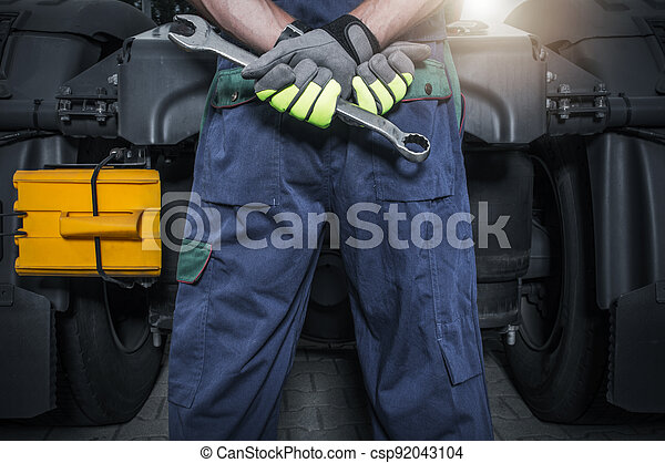 Truck Mechanic in Front of Tractor with Wrench in His Hands - csp92043104