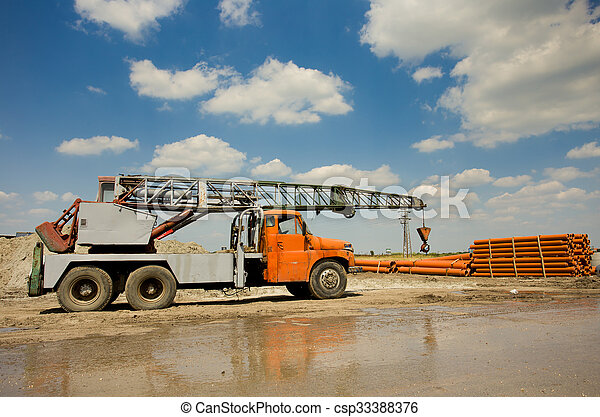 Truck with crane working at construction site - csp33388376