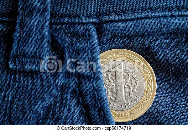 Turkish coin with a denomination of 1 lira in the pocket of old blue denim jeans - csp56174719