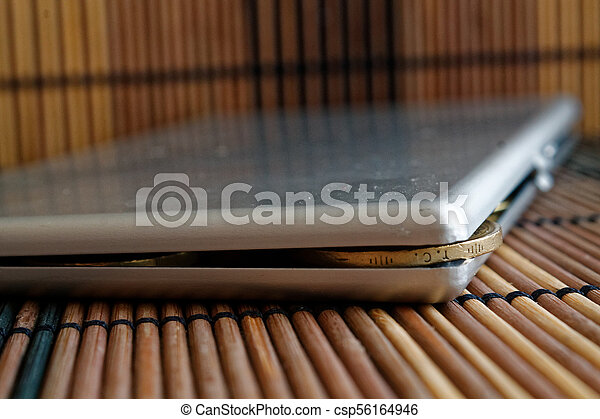Turkish coin with a denomination of 1 lira in steel wallet lies on wooden bamboo table background - csp56164946