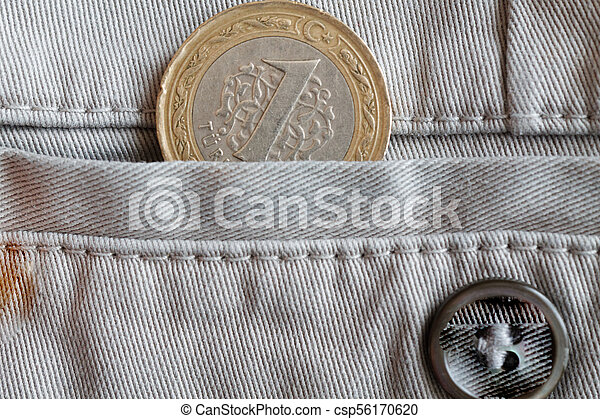 Turkish coin with a denomination of 1 lira in the pocket of beige denim jeans with button - csp56170620