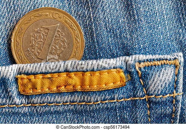 Turkish coin with a denomination of 1 lira in the pocket of old biege denim jeans - csp56173494