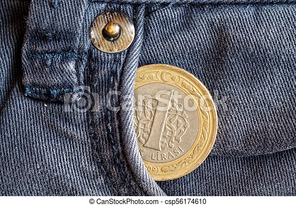 Turkish coin with a denomination of one lira in the pocket of obsolete blue denim jeans - csp56174610