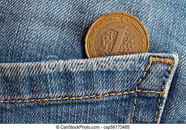 Turkish coin with a denomination of one lira in the pocket of old blue worn denim jeans - csp56173485