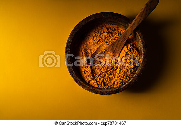 Turmeric powder in wooden bowl with wooden spoon on yellow background. Closeup view. Low key image with copy space - csp78701467