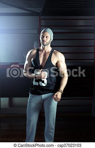 Ein Mann, der in der Turnhalle posiert - csp37023103