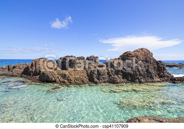 Turquoise pool on rocky tropical sea shore - csp41107909