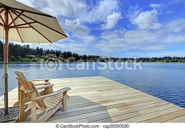 Two Adirondack Wooden Chairs With Umbrella On Dock Facing Blue Lake.    Csp38300590