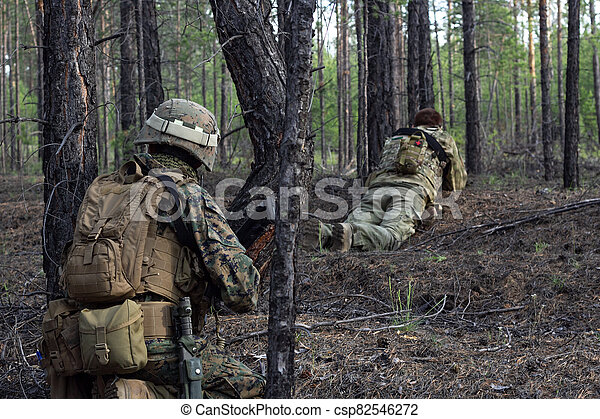 Two american soldiers are on a stakeout in the summer forest, waiting for the enemy, active military game airsoft - csp82546272