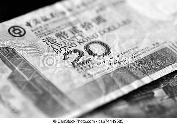 Two banknotes of twenty Hong Kong dollars on a dark background close-up. Black and white - csp74449585