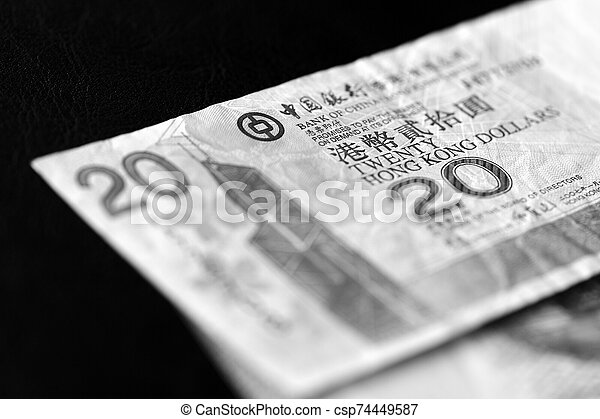 Two banknotes of twenty Hong Kong dollars on a dark background close-up. Black and white - csp74449587