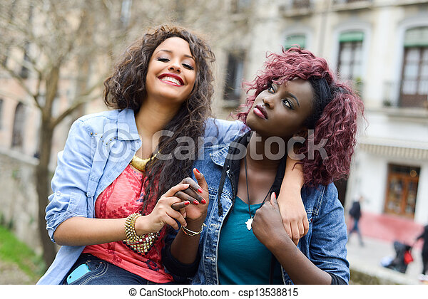 Two beautiful girls in urban backgrund, black and mixed women - csp13538815