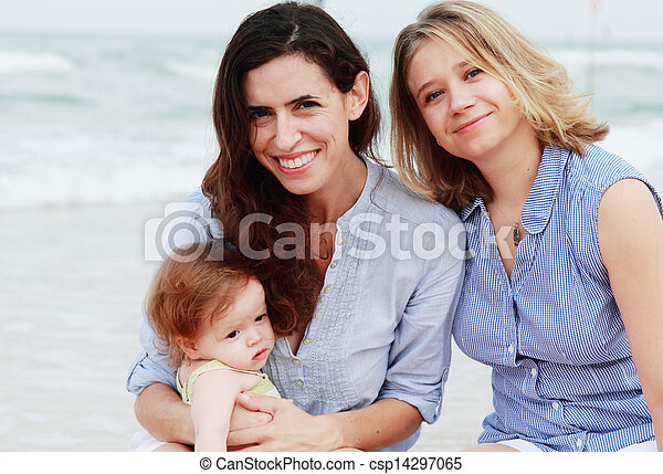 two beautiful girls with a baby on the beach - csp14297065