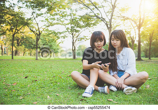 8d614125e3e Two beautiful happy young asian women friends having fun together at park  and taking a selfie. happy hipster young asian girls smiling and looking at  ...