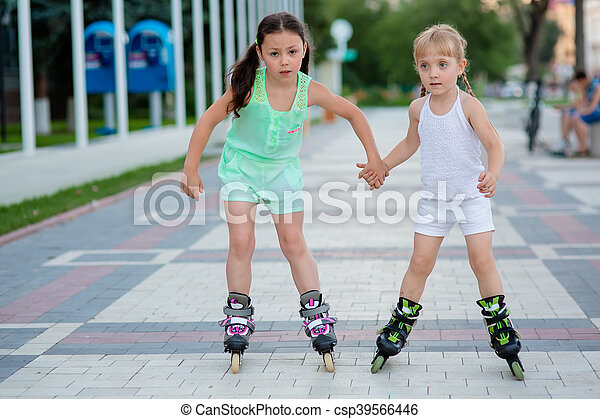 two beautiful little sisters in a roller skates - csp39566446