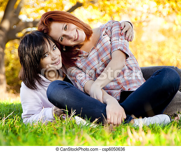 Two beautiful teen girl at green grass in the park. - csp6050636