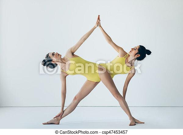two beautiful women doing yoga asana extended triangle