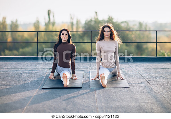 two beautiful women sitting on monkey pose on the roof