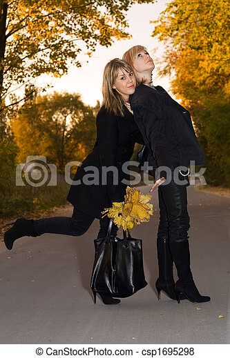Two beauty young blondes with autumn leaves on a road - csp1695298