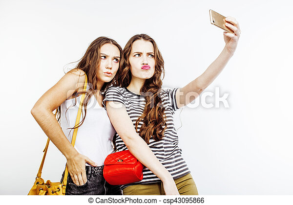 two best friends teenage girls together having fun, posing emotional on white background, besties happy smiling, making selfie, lifestyle people concept - csp43095866