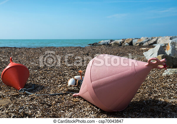 Two big buoys on the beach, azure sea and the rocky beach - csp70043847