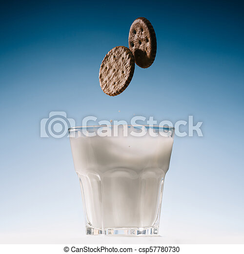 Two biscuits falling into glass of milk isolated on blue background - csp57780730