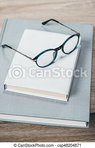 Two books and eyeglasses on table - csp48204871