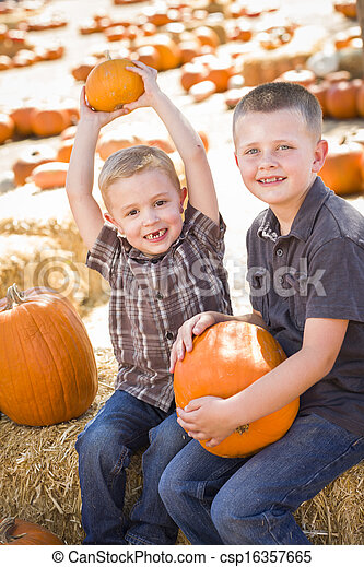 Two Boys at the Pumpkin Patch Talking and Having Fun  - csp16357665