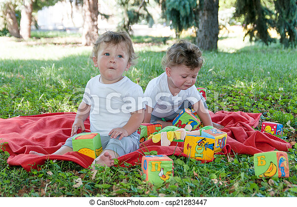 two boys twins sitting on a red blanket with toys in nature - csp21283447