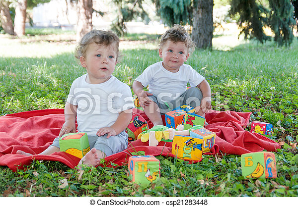 two boys twins sitting on a red blanket with toys in nature - csp21283448
