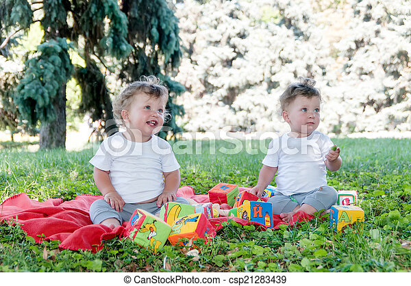 two boys twins sitting on a red blanket with toys in nature - csp21283439