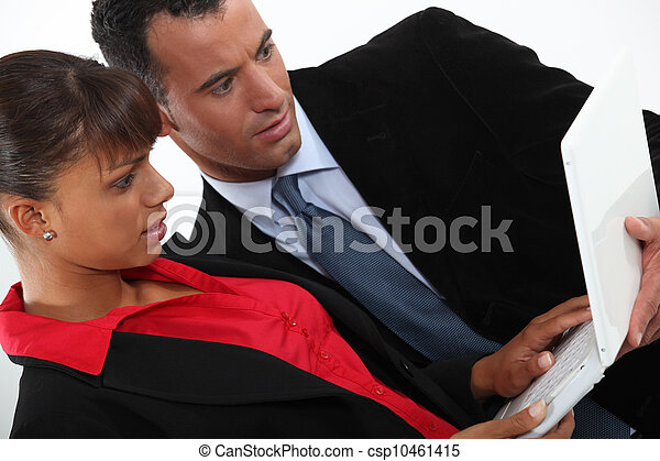 Two business people stood working on laptop - csp10461415