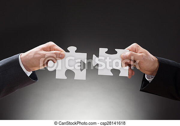 Two Businesspeople Holding Jigsaw Puzzle Pieces - csp28141618