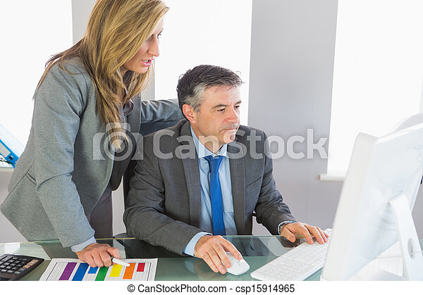 Two businesspeople looking at something on computer - csp15914965