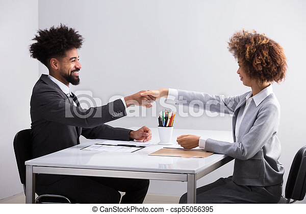 Two Businesspeople Shaking Hands - csp55056395