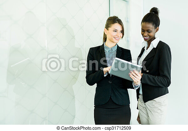 Two businesswomen looking at a tablet with a glass reflection - csp31712509