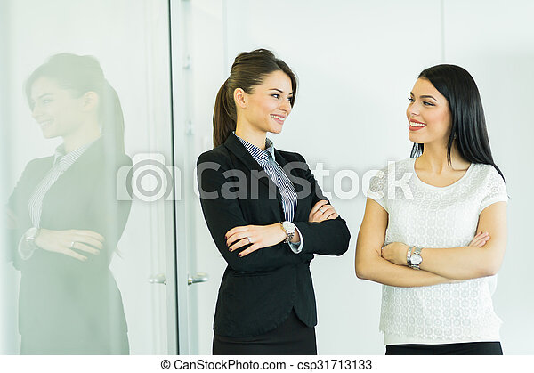 Two businesswomen talking in an office with reflection - csp31713133