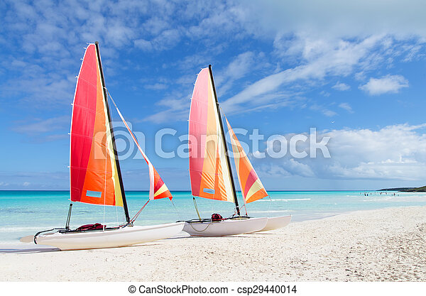 Two catamarans with its colorful sails wide open on Cuban white sandy beach - csp29440014