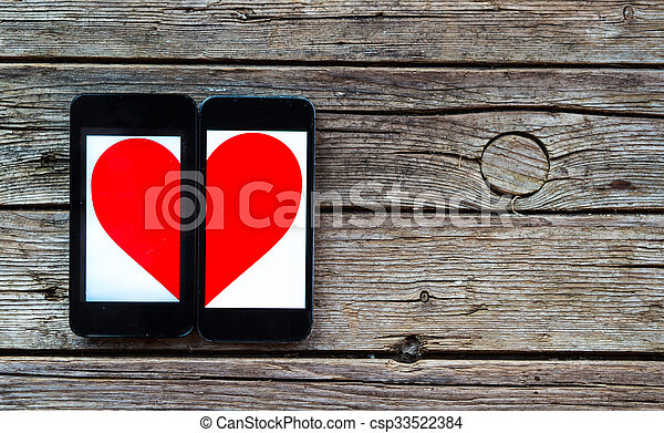 Two Cellphones With Half Heart Symbol On Wooden Background