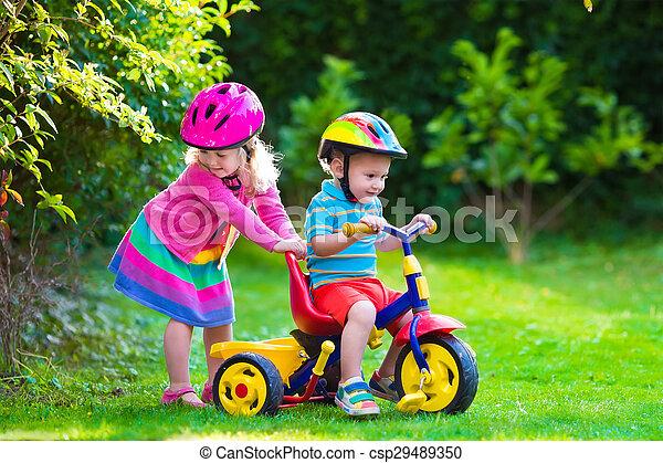 58a6eba57be Two children riding bikes. Kids riding bikes in a park. children ...