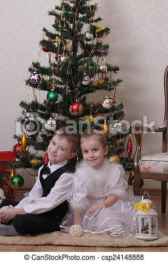 Two children sitting under Christmas tree - csp24148888
